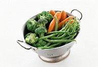 Beans, carrots and broccoli in a metal strainer