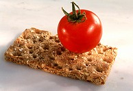 A crispbread and a whole tomato