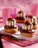 Individual round chocolate eclair and cream cakes