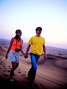 Young western couple walking through the desert in the United Arab Emirates