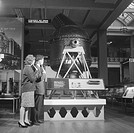 Museum visitors looking at a Bessemer converter, using a hand-held radio receiver and earphone intended for receiving signals from a low-powered trans...