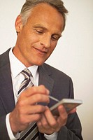 mature businessman making notes on electronic organizer