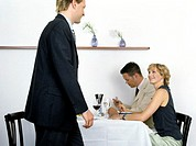 businessmen having lunch, woman glancing at man passing by