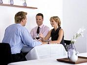three businessmen sitting in a restaurant