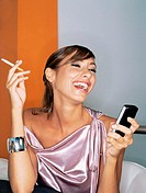 Young woman with mobile phone and cigarette