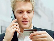 Man on mobile with credit card
