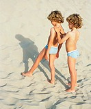Twins standing on the beach