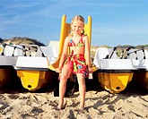 Girl sitting on boat slide