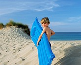 Boy with inflatable on edge of sand dune