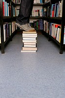 Person standing on books in library