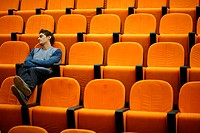 Drowsy young man alone in lecture theatre
