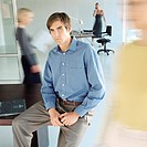 Man sitting on edge of desk in busy office