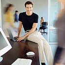 Man sitting on edge of desk in busy office (thumbnail)