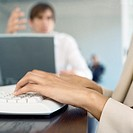 Businesspeople in office, close-up of hands on keyboard