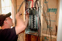 Electrician installing fans, lights, circuit panels and breakers on ladder