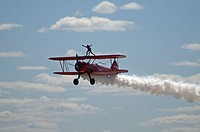 Carol Pilon performing wingwalking on Stearman biplane during airshow. Bagotville military base, Quebec, Canada