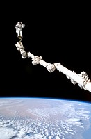Astronaut Stephen K. Robinson, STS-114 mission specialist, anchored to a foot restraint on the International Space Station´s Canadarm2, participating ...