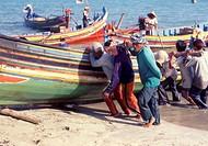 Fishermen pushing boat onto the beach, Terengganu, Malaysia