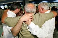 Men hugging. Betancourt Family Reunion, Cuban immigrants, Hispanic. Community Center. Key Biscayne, Florida. USA.