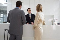 receptionist giving explanation to businessman and businesswoman