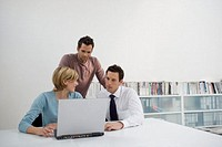 three people sitting around laptop