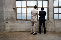 two businessmen looking out of window in empty building