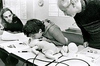 Infant CPR training. Woman being taught how to perform cardiopulmonary resuscitation (CPR) on an infant, using a mannequin. CPR is a combination of ar...
