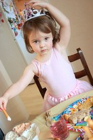 3 year old girl at a party, wearing a crown, with a table full of food in front of her