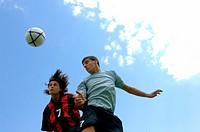 Soccer players jumping for the ball