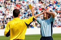 Referee showing yellow card to disappointed player