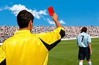 Referee showing red card to disappointed player