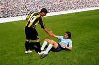 Soccer player helping opponent