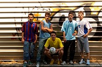 Group of teenage soccer friends against graffiti wall
