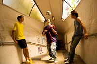Teenage boys heading ball in tunnel