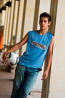 Teenage boy with ball leaning against pillar