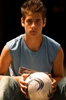 Portrait of teenage boy with soccer ball