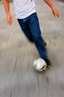 Man dribbling soccer ball in street