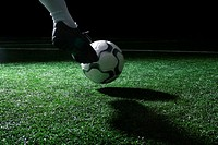 Close-up of foot kicking soccer ball