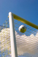 Soccer ball flying into top corner of goal
