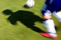 Shadow of soccer player running with ball