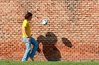 Young man juggling soccer ball in front of brick wall