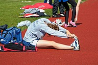 High School Track and Field event: stretching muscles before racing