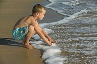 Little boy playing with the waves on a sand beach