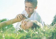 Boy and girl playing in grass