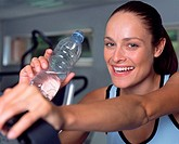 Woman drinking water in a gymnasium