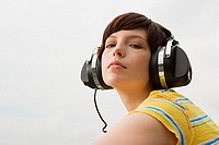 Young woman listening to music on roof