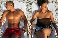 Young couple in sun loungers