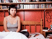 Teenage girl sitting on bed