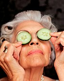 Close-up of woman holding cucumbers over eyes