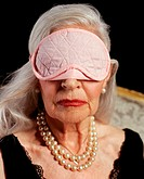 Senior adult woman wearing pink eye mask